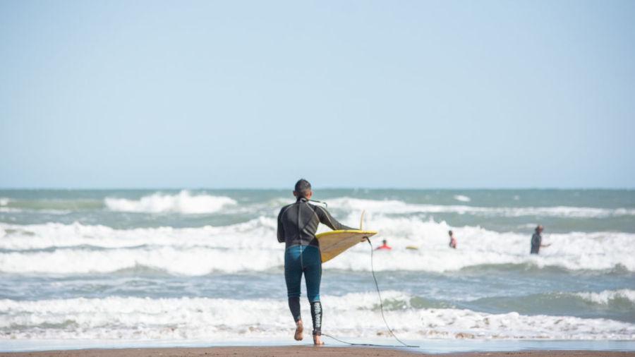 Full length of man standing on beach against clear sky