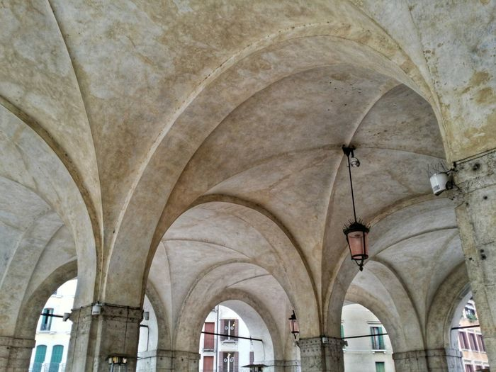 Low angle view of old lamp hanging from historic building ceiling