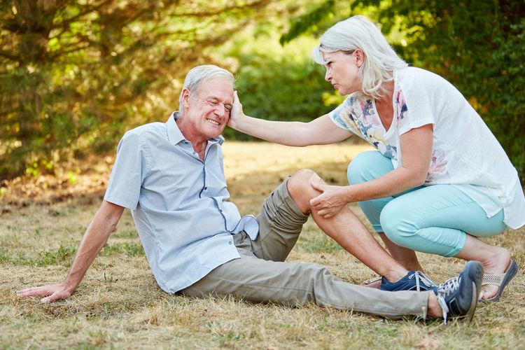Woman applying bandage to senior man at park