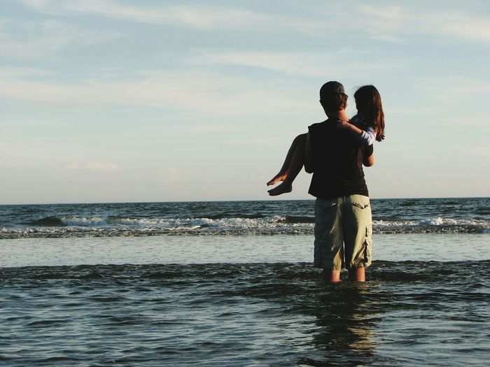 Rear View Of Father Carrying Daughter In Sea Against Sky