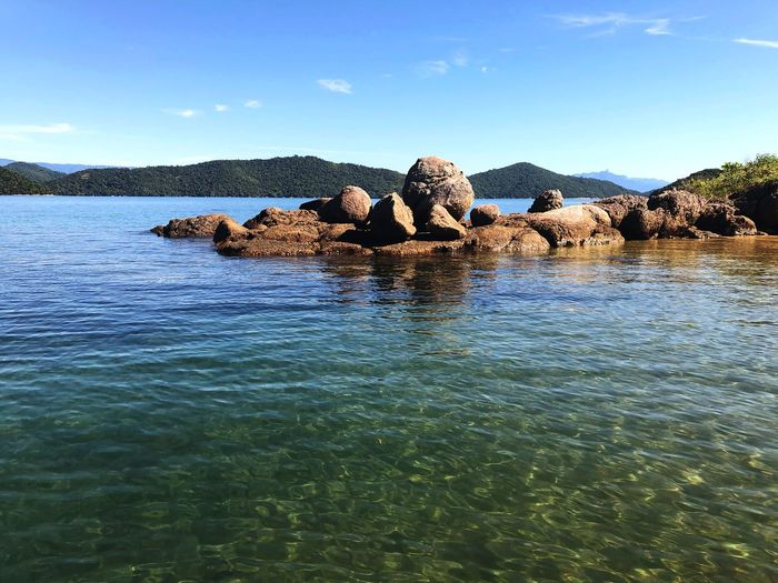 Water Sky Nature Waterfront Day No People Tranquility Sea Beauty In Nature Sunlight Scenics - Nature Blue Tranquil Scene Non-urban Scene Tree Rock Solid