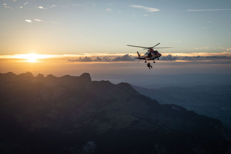 Military Man Getting Down From Helicopter Against Sky During Sunset