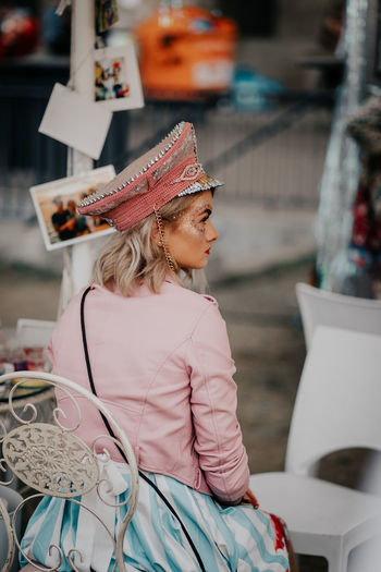 Midsection of woman wearing hat sitting outdoors