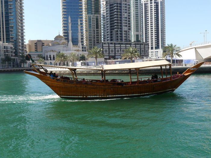 Dhow Underway on the Marina, Dubai, United Arab Emirates 2019 Dubai UAE 2019 Marina Nautical Vessel Dhow Boat Wooden Boat Transportation Water Mode Of Transportation Waterfront Sea No People Blue Sky Underway Wake - Water Glassy Water Ripples In The Water Traditional Boat Sunlight And Shadow Palm Trees Mosque Composition Outdoor Photography
