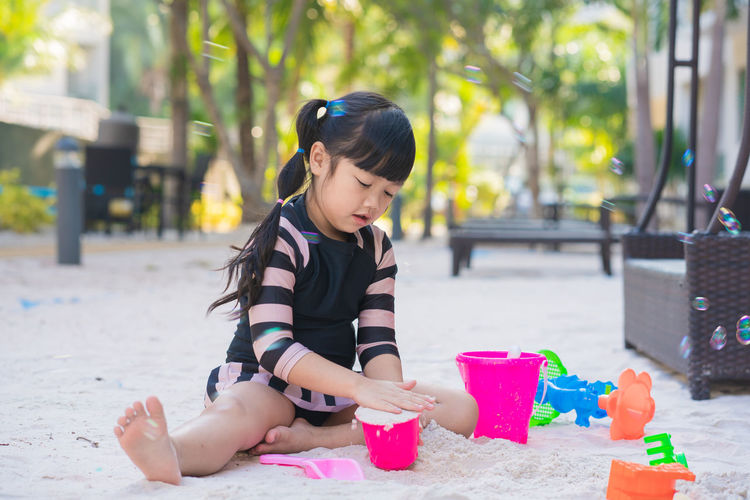 Cute girl playing with toy sitting outdoors