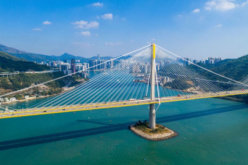 Suspension bridge over sea against blue sky during sunny day