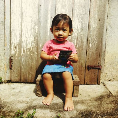Portrait Of Cute Girl Holding Mobile Phone While Sitting Outdoors
