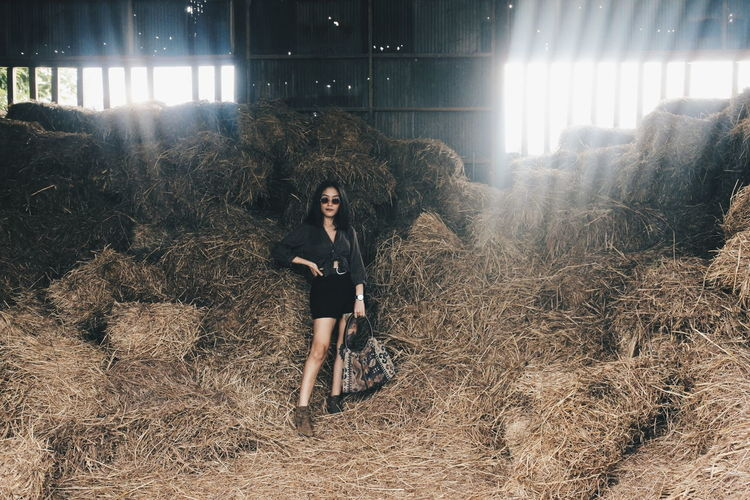Portrait of woman standing by hay bales in shed