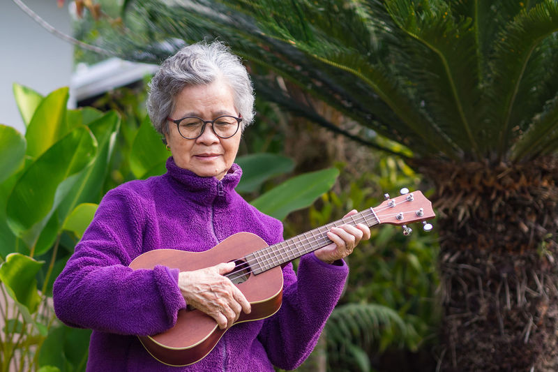 Portrait of an elderly woman playing ukulele while standing in a garden