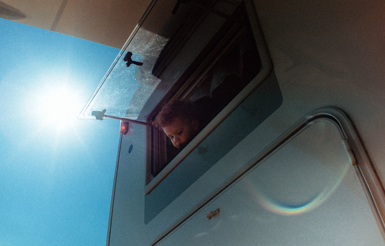 Little girl looking through window of trailer on sunny day