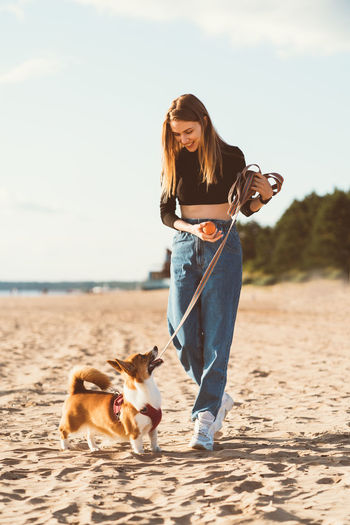 Full length of young woman with dog on beach