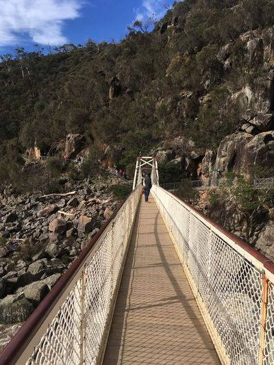Man standing on footbridge against mountain