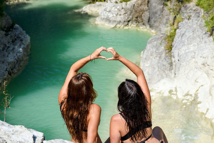 Two women forming a hart shape with hands. outdoors, nature, water.