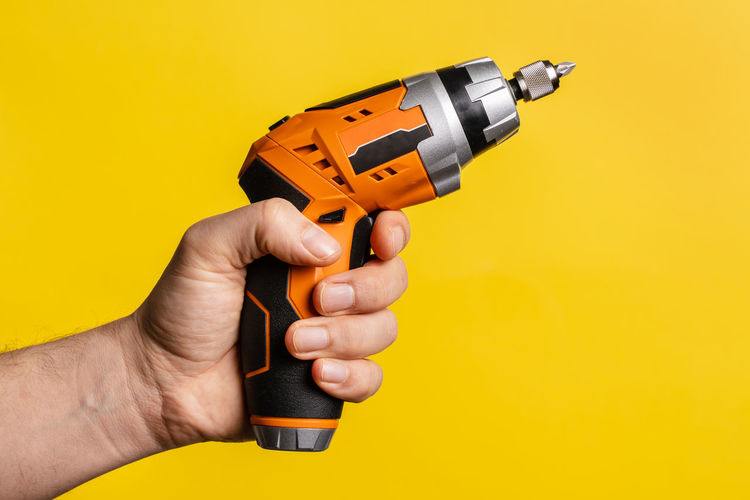 Close-up of man holding cigarette against orange background