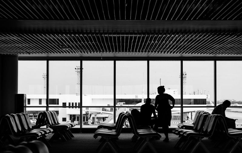 Adult Airport Airport Departure Area Airport Terminal Business Chair Day Glass - Material Indoors  Lifestyles Men People Real People Seat Sitting Table Transparent Transportation Travel Waiting Window