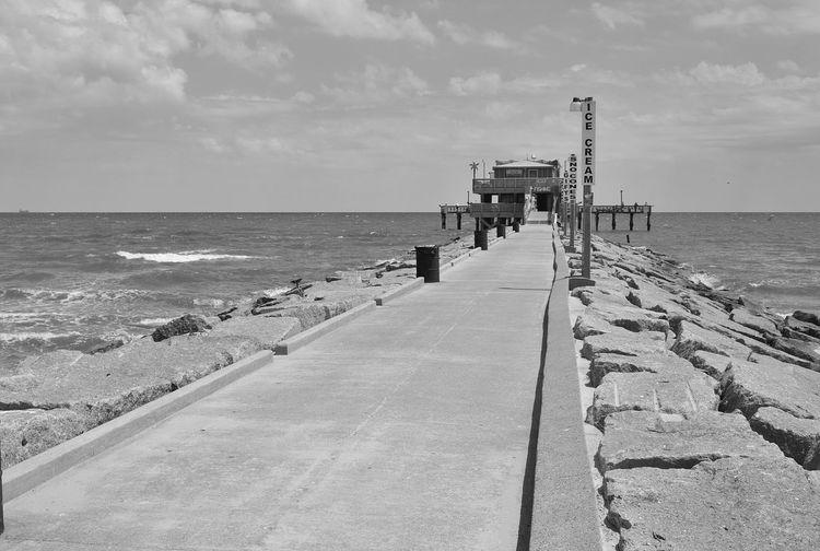 Pier amidst sea against cloudy sky
