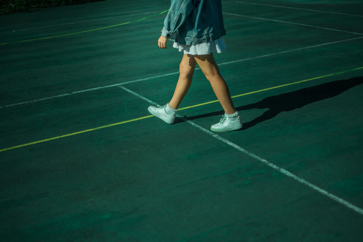 Low Section Of Young Woman Walking In Tennis Court
