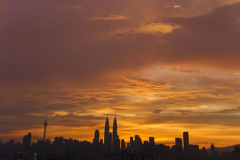 Silhouette of cityscape against orange sky during sunset