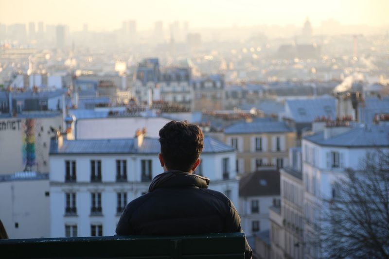 Rear view of man sitting on bench against cityscape