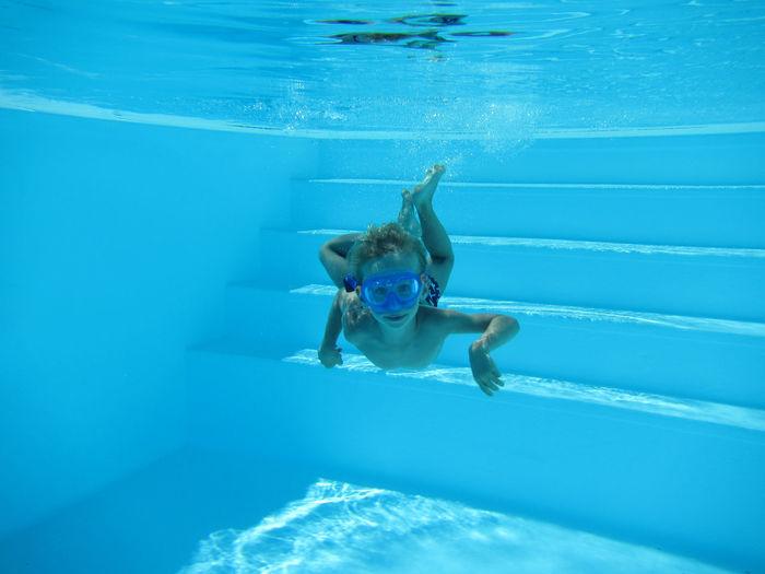 Boy diving underwater in swimming pool