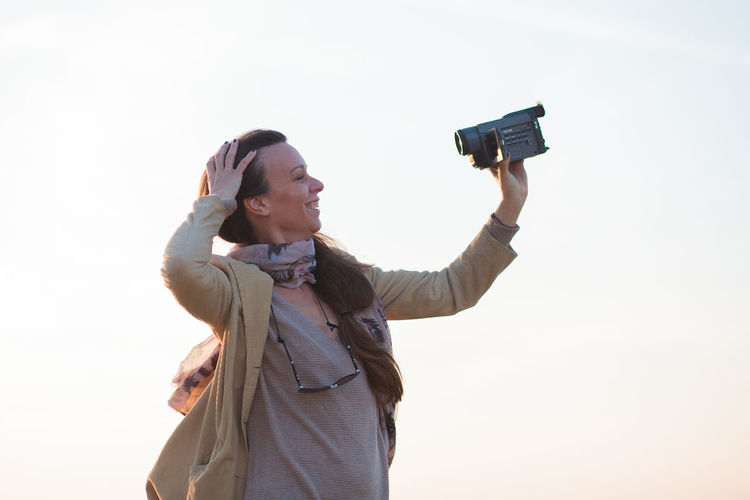 Young woman photographing with camera