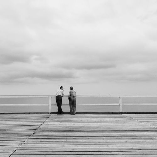 Rear View Of Friends Standing On Pier Over Sea
