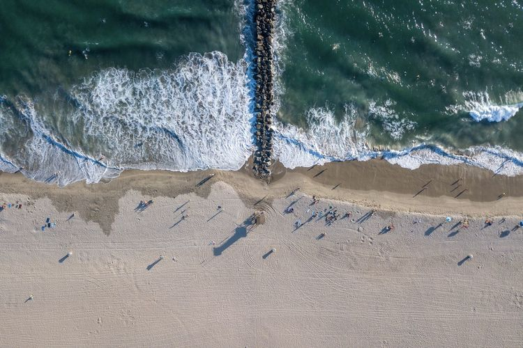 aerial drone view of waves crashing on a busy beach by a rocky jetty Newport Beach, CA, USA Aerial Photography Aquatic Sport Beach Beachphotography Beauty In Nature Day Drone View High Angle View Jetty Land Motion Nature No People Non-urban Scene Outdoors Power In Nature Sand Scenics - Nature Sea Sport Sunlight Water Wave Waves