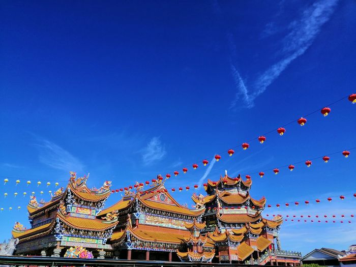 Low angle view of decorations hanging against blue sky
