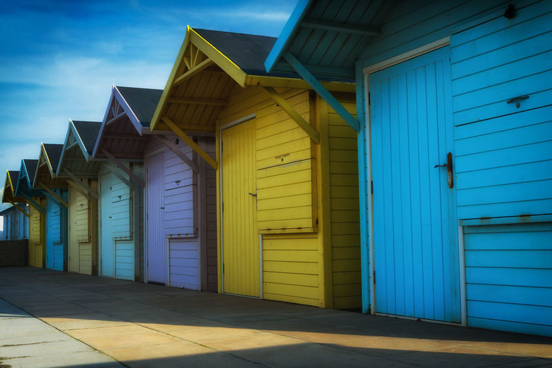 A colourful row of beach huts on the seafront of the Lancashire seaside town of Fleetwood, England, UK Bright Bright Colors Colourful Lancashire Promenade Sun And Shadow Architecture Beach Huts Blue Building Exterior Built Structure Closed Coast Day Door Fleetwood Multi Colored No People Outdoors Receding Shore Sky Symmetry Wood - Material Wooden