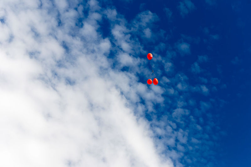 Low angle view of red balloons flying against blue sky