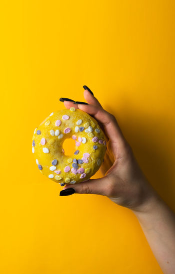 Midsection of person holding ice cream against yellow background