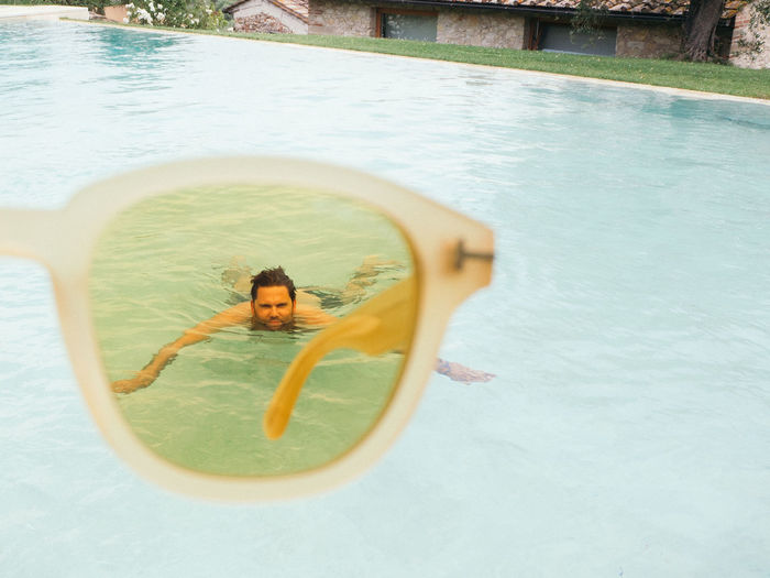 High angle view of man swimming in pool seen through sunglasses