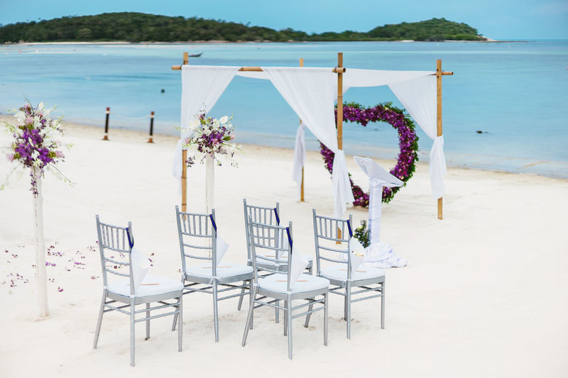Beach wedding venue setting for small size on the white sand with turquoise sea and panoramic ocean view Banquet Nature Ocean View Romantic Setting Aisle Arch Beach Beauty In Nature Bouquet Chair Coastal Decoration Flower Heart Shape Island Nature No People Outdoors Sand Sea Seat Tranquility Turquoise Water White Sand