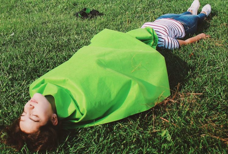 Woman wrapped in green blanket sleeping with female friend on grassy field