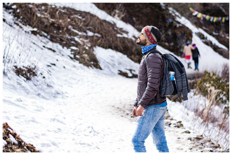 Side view of young man with backpack standing on snowcapped mountain
