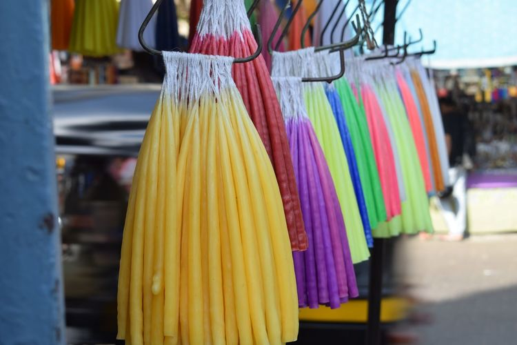 Close-up of colorful candles hanging for sale in market