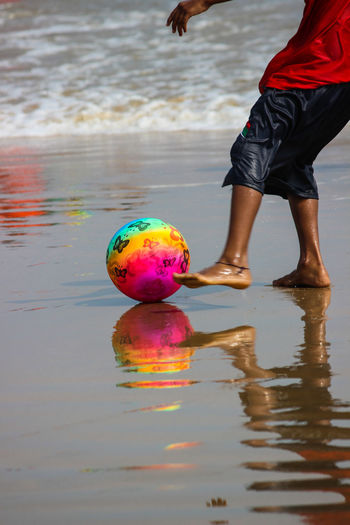 Low section of man playing with ball on shore at beach