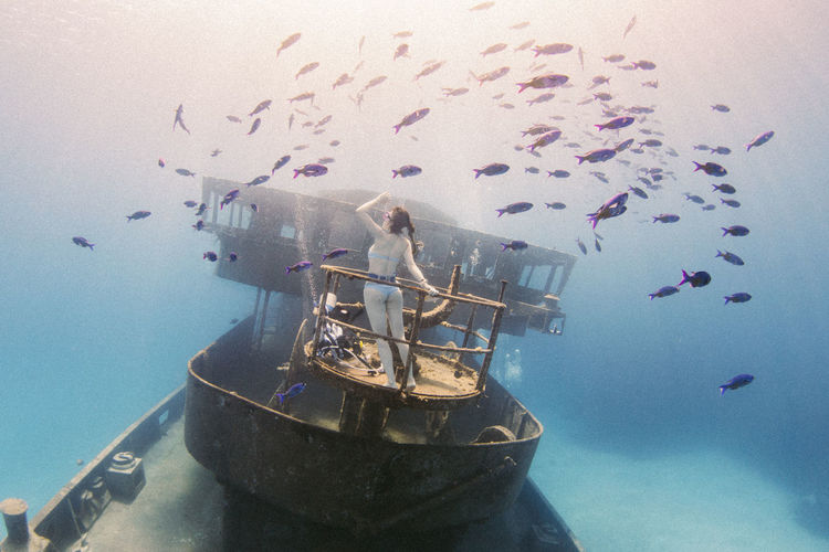 Woman on abandoned boat surrounded by fish in sea