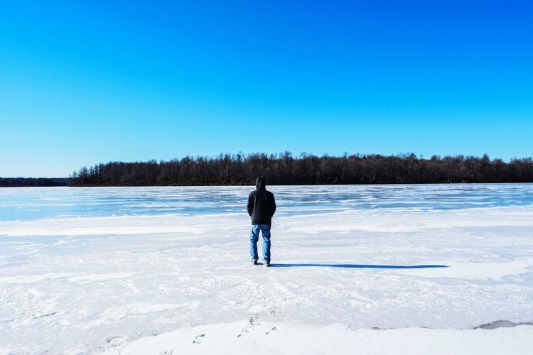 Rear view of man looking at frozen lake against clear blue sky