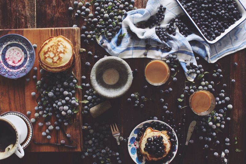 Directly above shot of blueberries and pancakes with tea on table