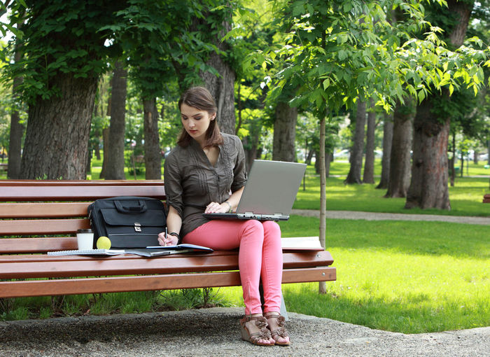 Woman working on a laptop on a bench in an urban park. Laptop Sitting Computer Using Laptop Wireless Technology One Person Technology Communication Young Adult Park Casual Clothing Park - Man Made Space Bench Woman Young Woman Student Learning Studying Nature Urban Park