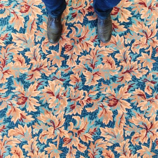 Low section of man standing on patterned carpet