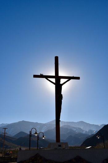 Cross on mountain against clear blue sky