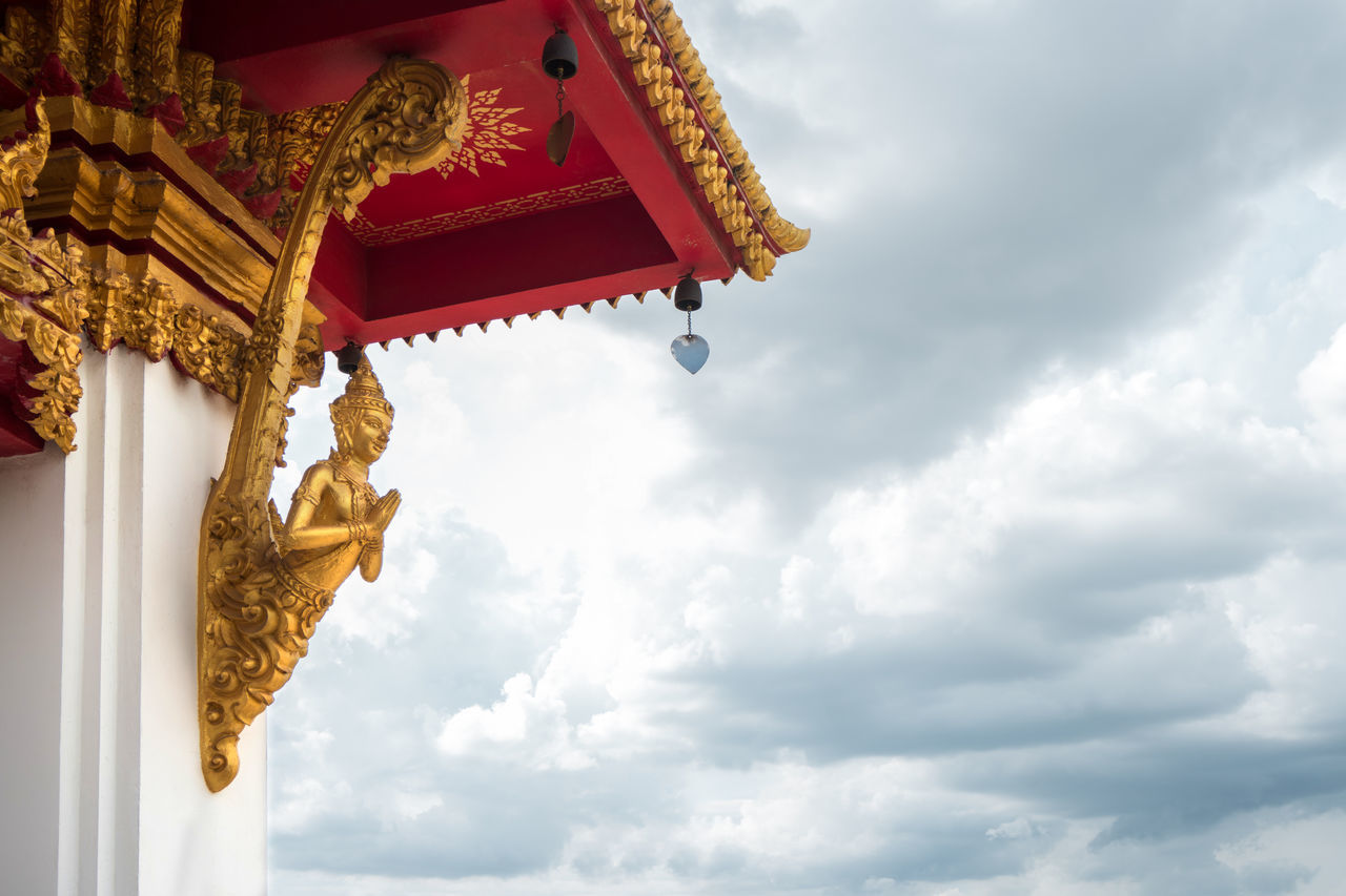 cloud - sky, low angle view, religion, gold colored, statue, spirituality, sculpture, sky, human representation, no people, place of worship, day, built structure, golden color, architecture, outdoors