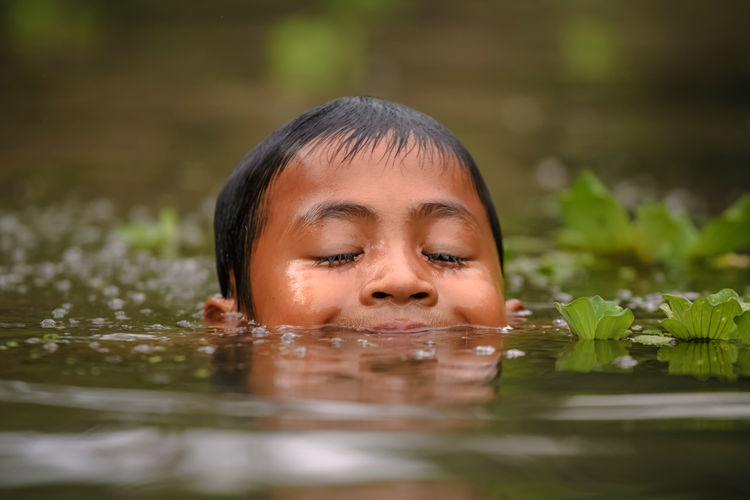 Close-up of boy swimming in river