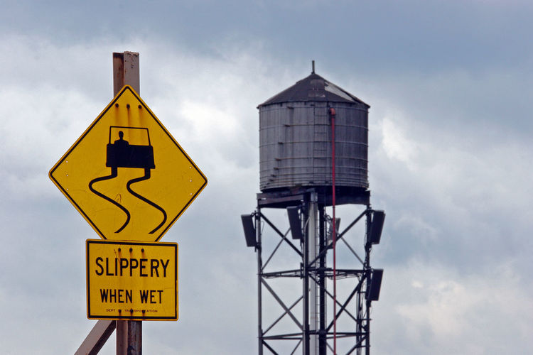 Warning sign and water tower against cloudy sky