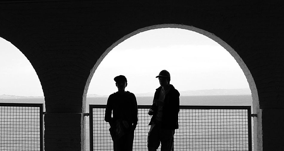Boys standing at arch window by sea against clear sky
