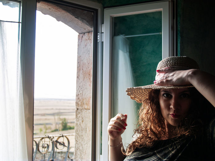Portrait Of Smiling Woman Standing By Window