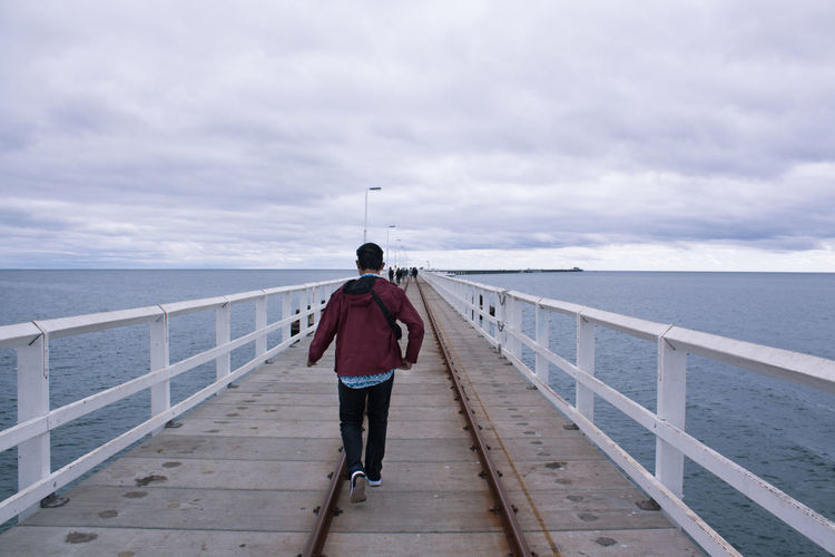 Rear view of man standing on jetty against sea