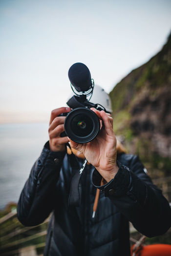 Man photographing with camera against sky